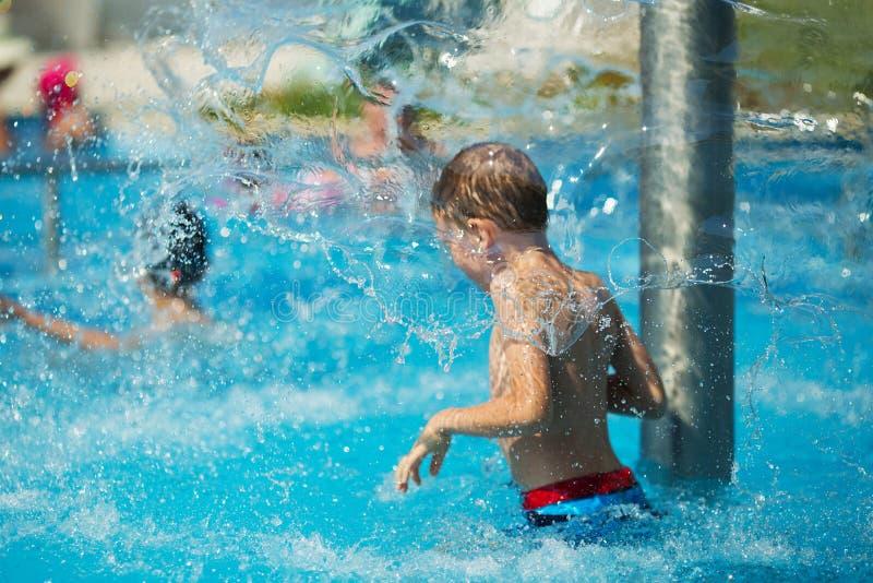 Het gelukkige jong geitje spelen in blauw water van zwembad op tropisch r royalty-vrije stock fotografie