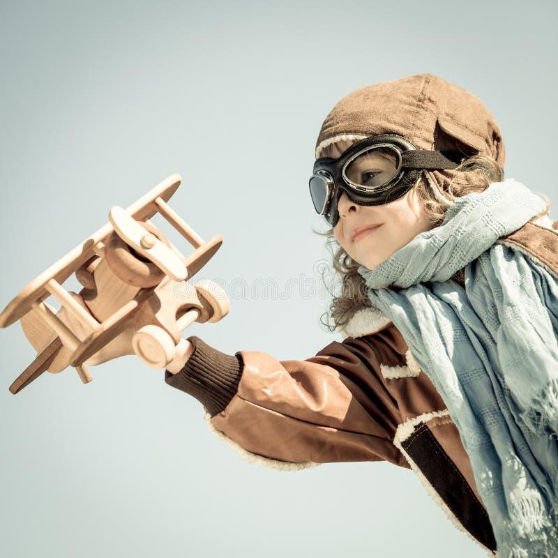 Het gelukkige jong geitje spelen met stuk speelgoed vliegtuig stock foto