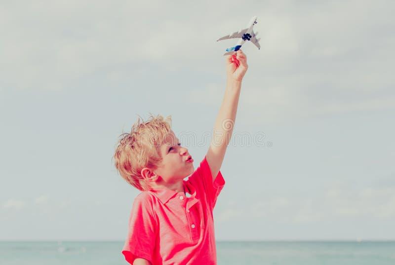 Het gelukkige jong geitje spelen met stuk speelgoed vliegtuig op blauwe hemel stock foto