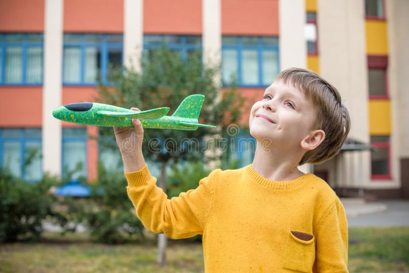 Het gelukkige jong geitje spelen met stuk speelgoed vliegtuig tegen aardige de bouwachtergrond De jongen werpt schuimvliegtuig op stock afbeeldingen