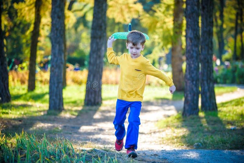 Het gelukkige jong geitje spelen met stuk speelgoed vliegtuig tegen de blauwe achtergrond van de de zomerhemel De jongen werpt sc stock foto
