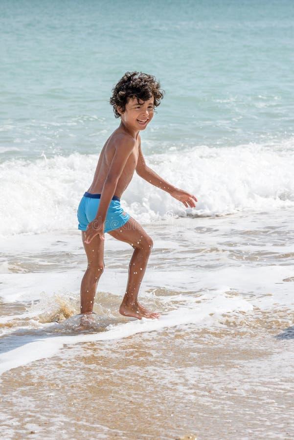 Het gelukkige jong geitje spelen op het strand in ruwe wateren tijdens een de zomervakantie stock foto's