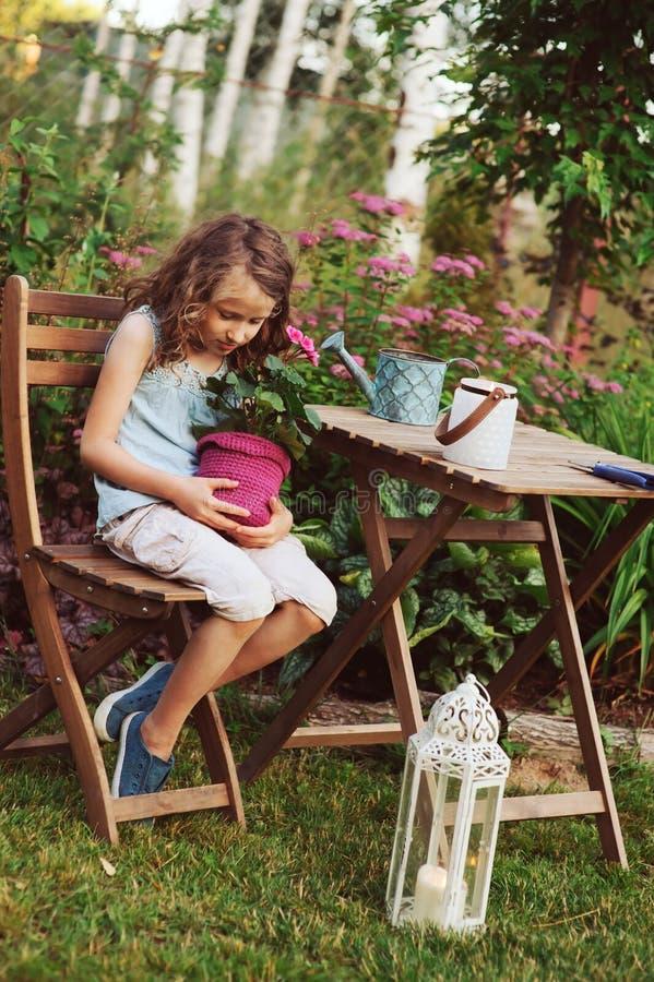 het gelukkige jong geitjemeisje spelen in de zomertuin, die geraniumbloem in pot houden royalty-vrije stock afbeeldingen
