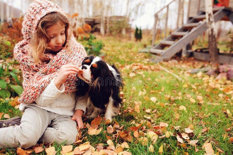 Het gelukkige jong geitjemeisje spelen met haar arrogante het spanielhond van koningscharles in de herfst stock afbeeldingen