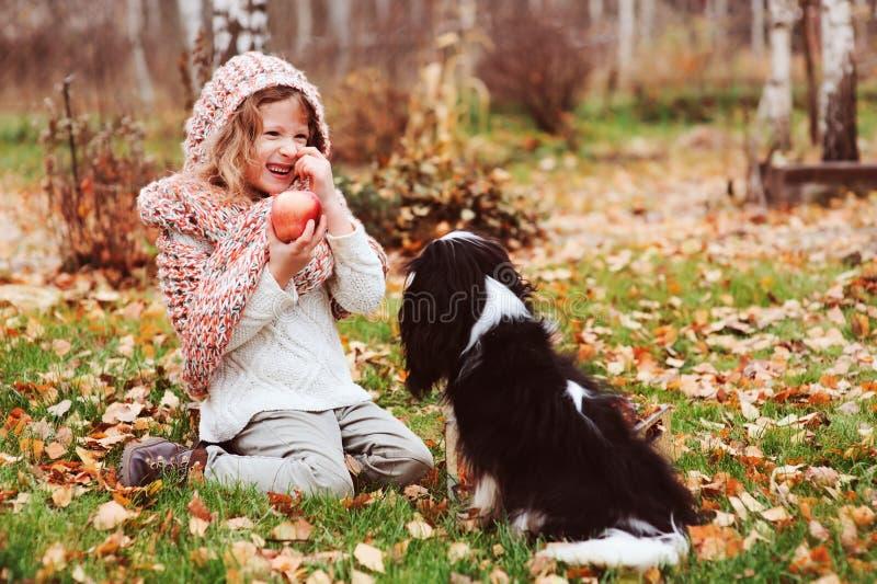 Het gelukkige jong geitjemeisje spelen met haar arrogante het spanielhond van koningscharles in de herfst stock foto's