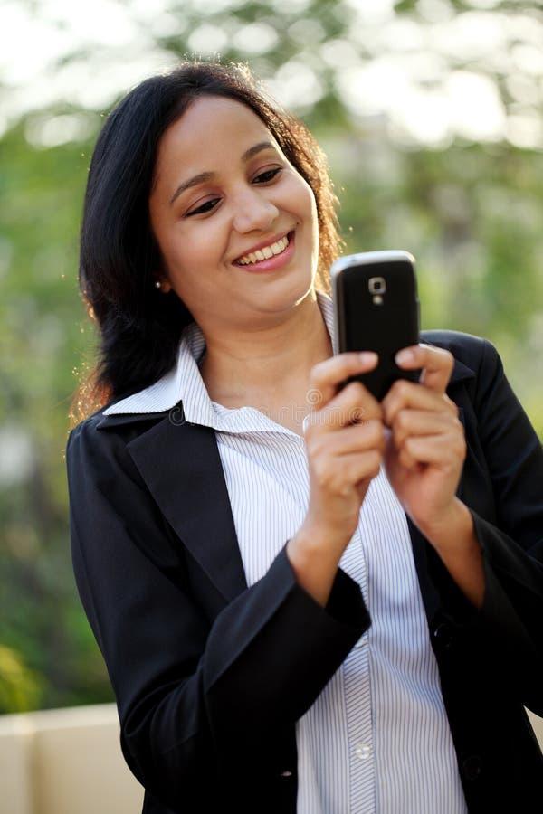 Het gelukkige jonge bedrijfsvrouw texting bij in openlucht stock afbeeldingen