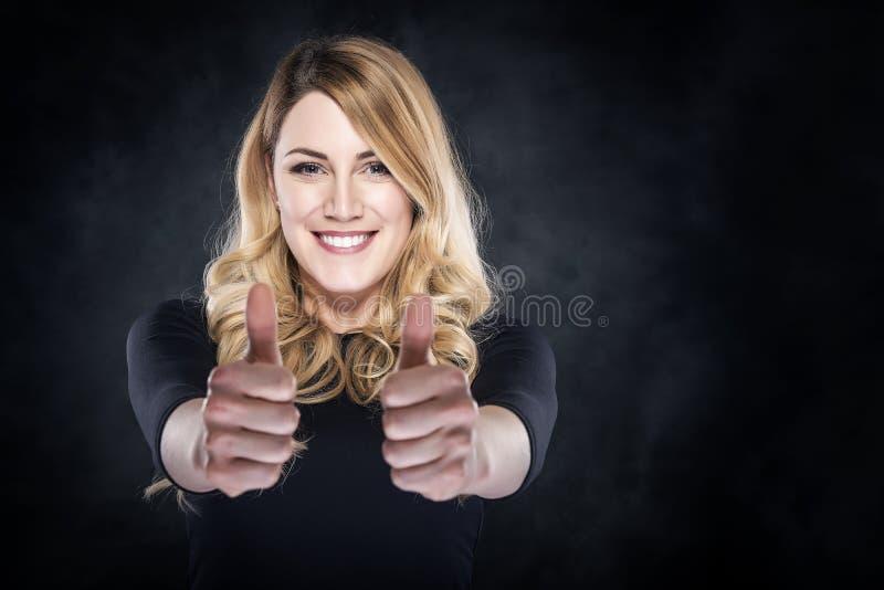 Het gelukkige jonge blondevrouw tonen beduimelt omhoog stock fotografie
