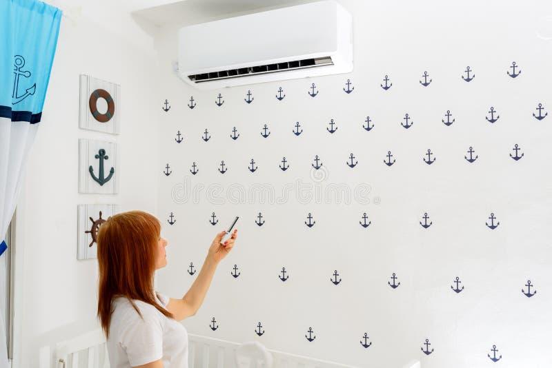 Het gelukkige Jonge de Afstandsbediening van de Vrouwenholding Ontspannen onder de Airconditioner royalty-vrije stock fotografie