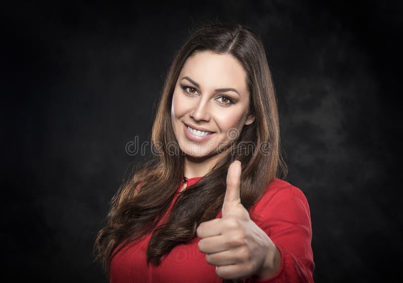 Het gelukkige jonge donkerbruine vrouw tonen beduimelt omhoog royalty-vrije stock fotografie