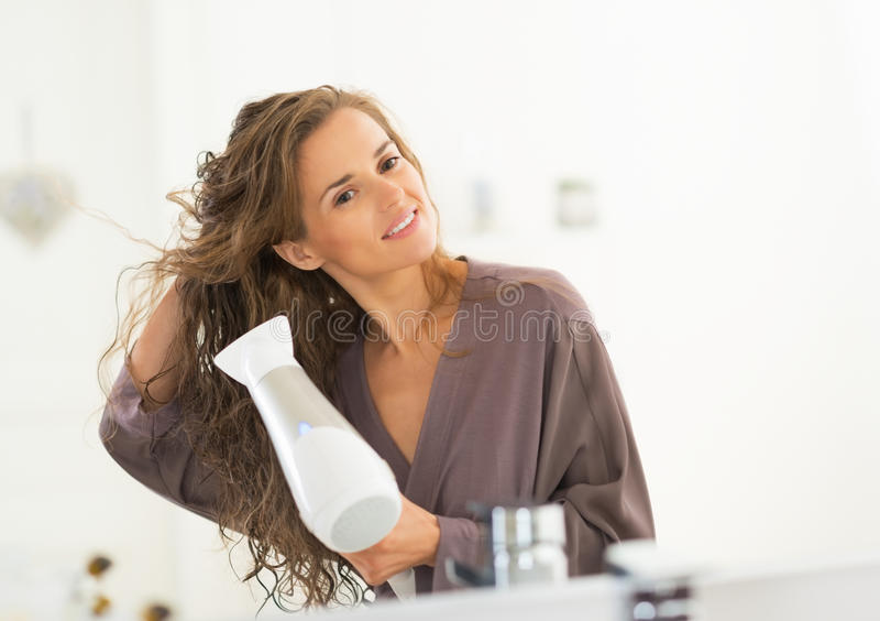 Het gelukkige jonge drogende haar van de vrouwenslag in badkamers stock afbeeldingen