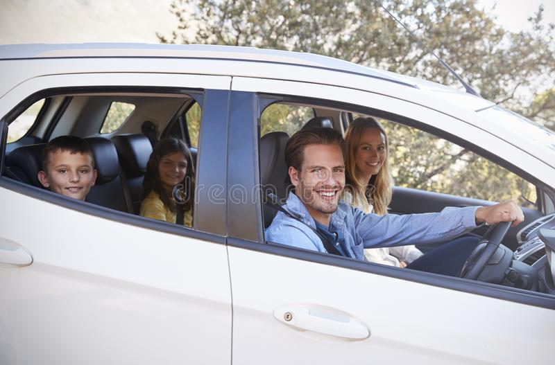 Het gelukkige jonge familie drijven in hun auto die aan camera kijken stock fotografie
