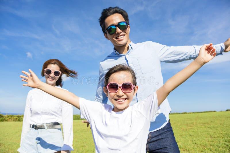 Het gelukkige jonge familie spelen op het gras royalty-vrije stock afbeeldingen