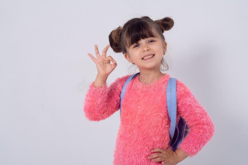 Het gelukkige jonge geitje met schooltas glimlacht en toont O.K. teken op witte achtergrond stock foto's