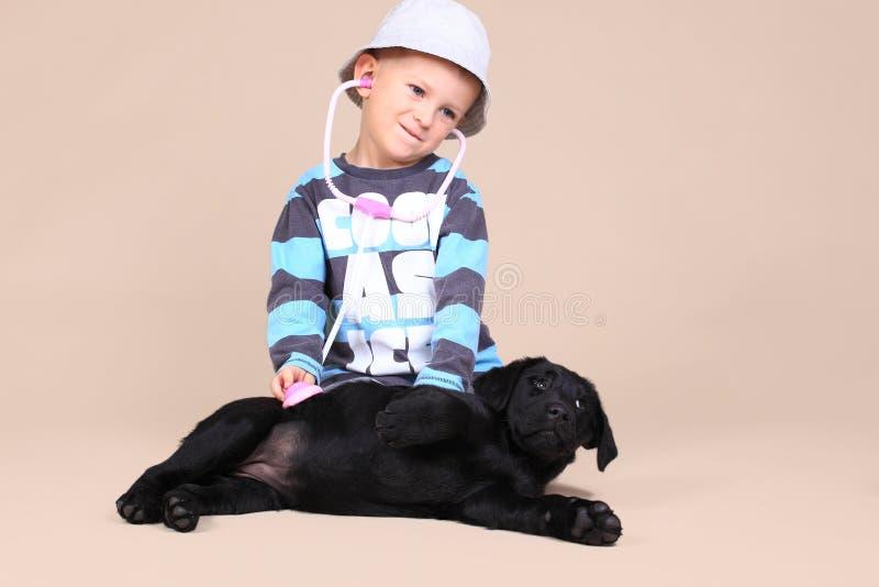 Het gelukkige jonge geitje onderzoekt puppy stock foto