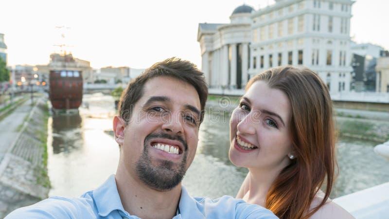 Het gelukkige jonge heteroseksuele echtpaar in liefde neemt selfie portret op de hoofdstraat van Skopje, Macedonië De mooie toeri royalty-vrije stock foto