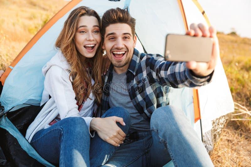 Het gelukkige jonge houdende van paar buiten in vrije alternatieve vakantie die neemt een selfie telefonisch kamperen royalty-vrije stock afbeelding