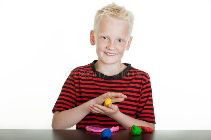 Het gelukkige jonge jongen spelen met modelleringsklei stock afbeelding
