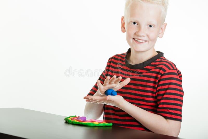 Het gelukkige jonge jongen spelen met plastic stopverf stock afbeeldingen