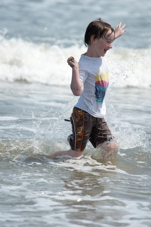 Het gelukkige jonge jongenskind lopende spelen van en het hebben van pret in de branding en de golven van een zandig zonnig stran stock foto's