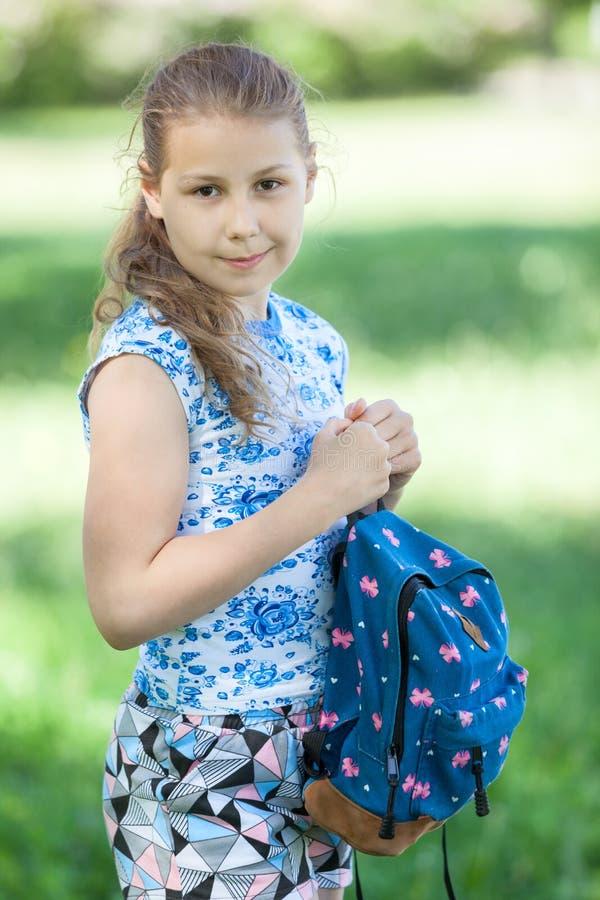Het gelukkige jonge meisje die van het blondehaar zich in park met kleine rugzak in handen bevinden, die camera bekijken royalty-vrije stock afbeeldingen