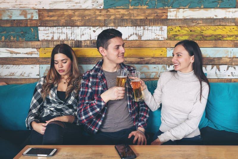 Het gelukkige jonge meisje het drinken bier met de jonge mens en socialiseert het negeren van jaloerse droevige vrouw royalty-vrije stock foto's