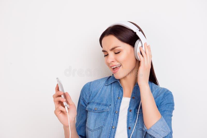 Het gelukkige jonge meisje geniet van luister aan muziek in hesdphones royalty-vrije stock foto's