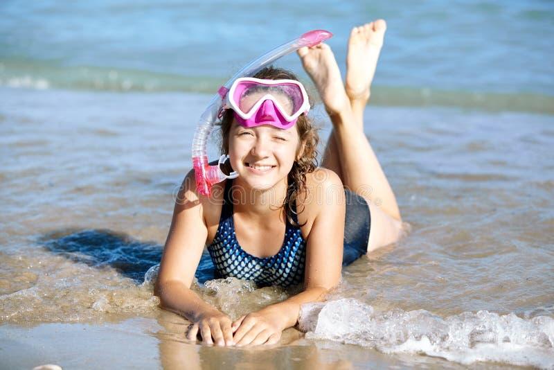 Het gelukkige jonge meisje ligt op het strand in vinnen en maskers voor vrij duiken royalty-vrije stock afbeelding