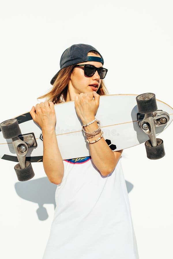 Het gelukkige jonge meisje met een skateboard rijden royalty-vrije stock foto's