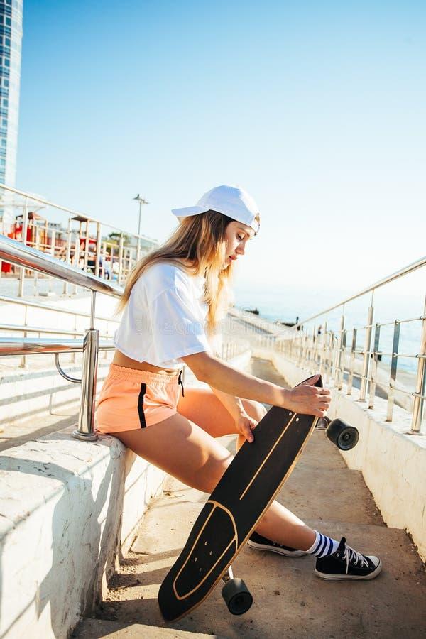 Het gelukkige jonge meisje met een skateboard rijden stock foto's