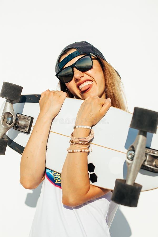 Het gelukkige jonge meisje met een skateboard rijden royalty-vrije stock afbeeldingen