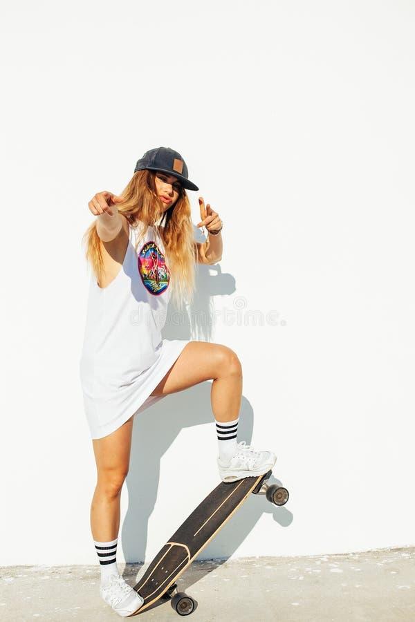 Het gelukkige jonge meisje met een skateboard rijden stock foto