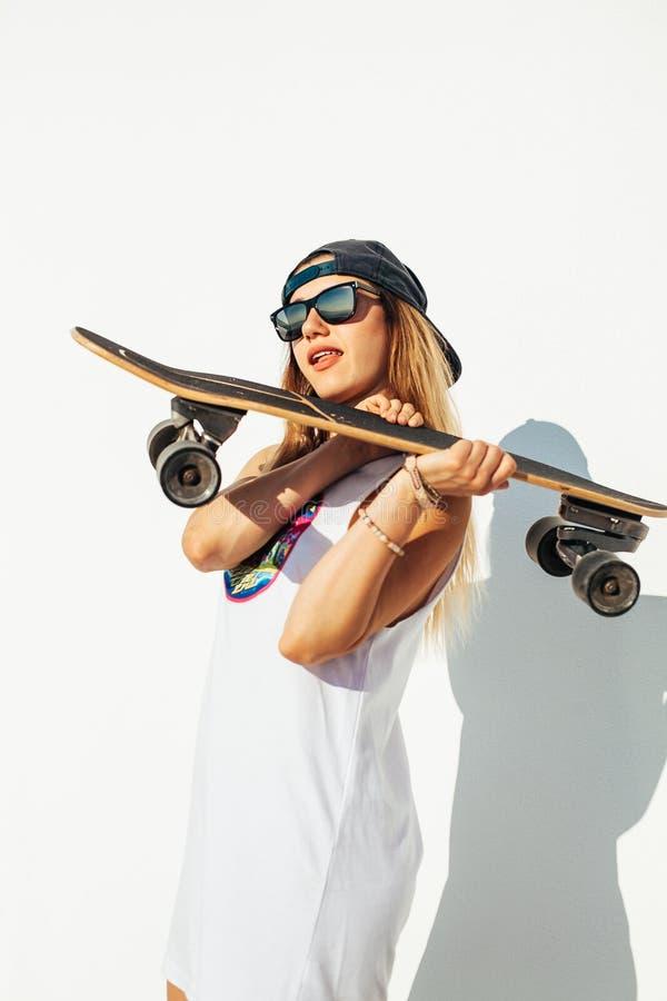Het gelukkige jonge meisje met een skateboard rijden stock afbeelding