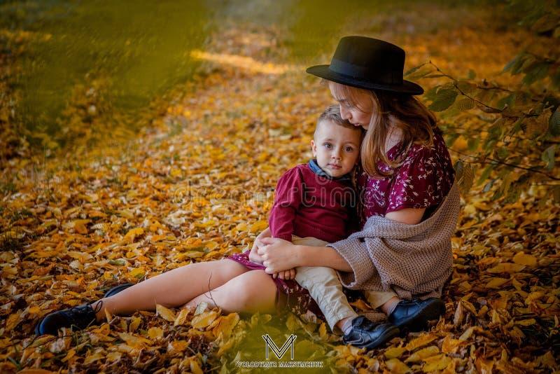 Het gelukkige jonge moeder spelen met baby in de herfstpark met gele esdoorn gaat weg Familie die in openlucht in de herfst lopen royalty-vrije stock foto