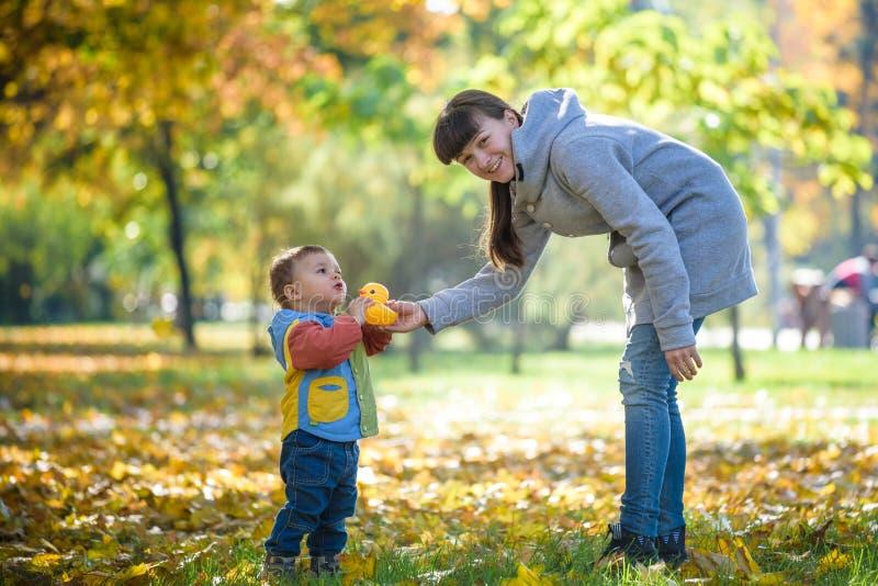 Het gelukkige jonge moeder spelen met baby in de herfstpark met gele esdoorn gaat weg Familie die in openlucht in de herfst lopen royalty-vrije stock fotografie