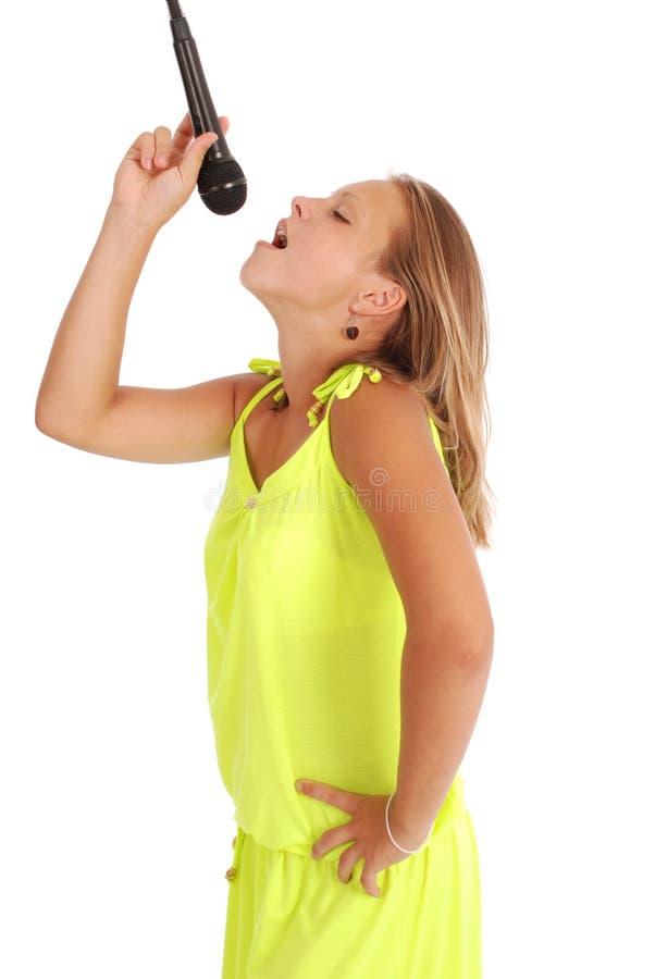 Het gelukkige jonge mooie meisje zingen met microfoon royalty-vrije stock afbeelding