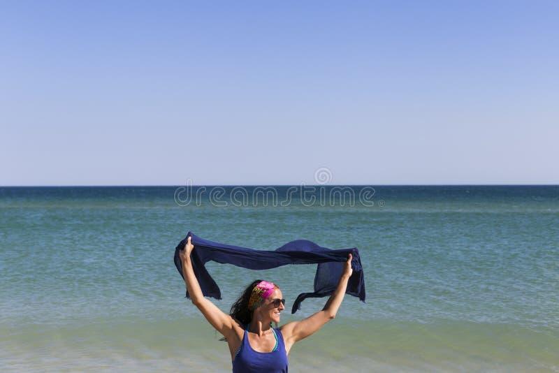 het gelukkige jonge mooie vrouw spelen met een blauwe sjaal bij het strand Pret, wind en levensstijl stock afbeelding