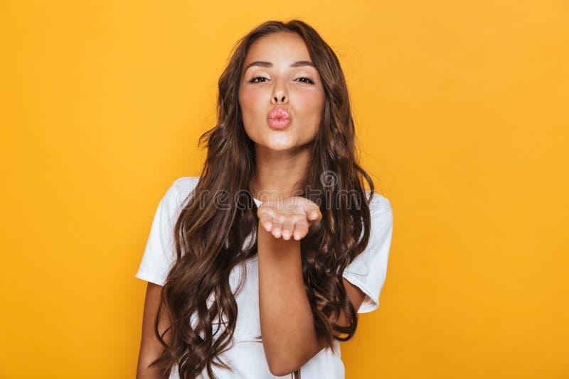 Het gelukkige jonge mooie vrouw stellen geïsoleerd over gele blazende kussen als achtergrond royalty-vrije stock fotografie
