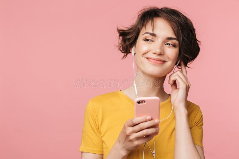 Het gelukkige jonge mooie vrouw stellen geïsoleerd over roze muur achtergrond het luisteren muziek met oortelefoons die mobiele t royalty-vrije stock fotografie