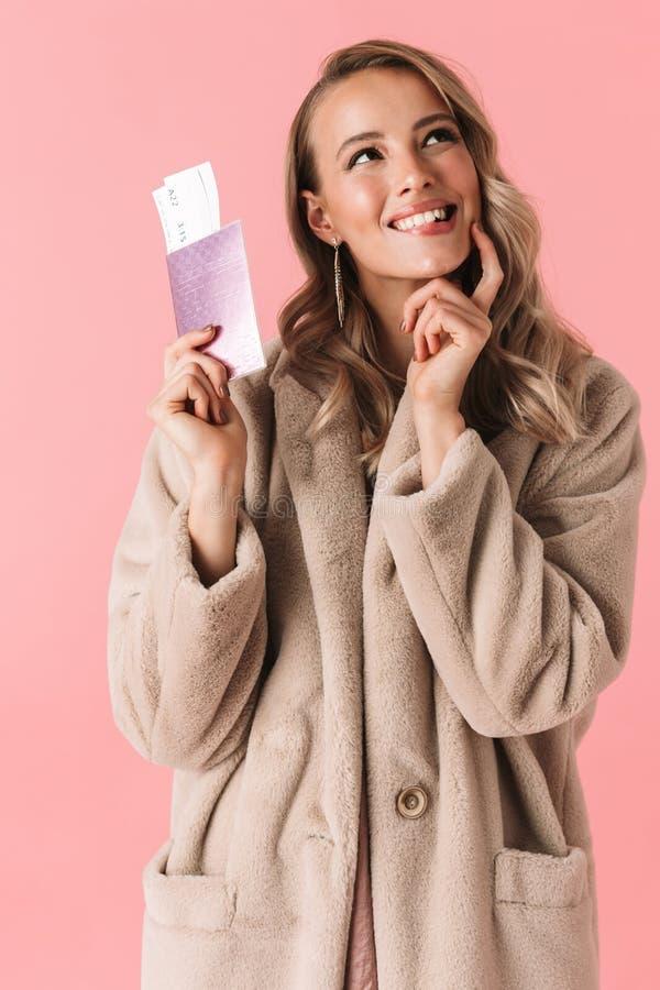 Het gelukkige jonge mooie vrouw stellen geïsoleerd over roze muur achtergrondholdingspaspoort met kaartjes royalty-vrije stock afbeeldingen