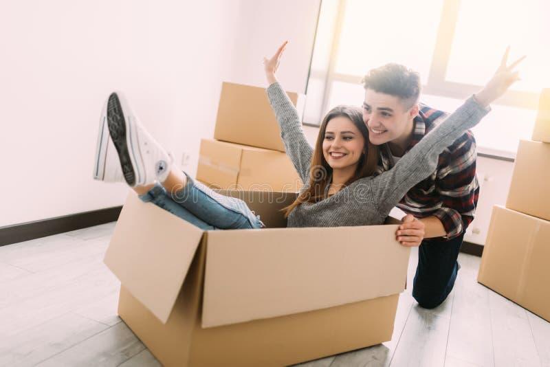Het gelukkige jonge paar heeft pret met kartondozen in nieuw huis bij het bewegen van dag stock foto's