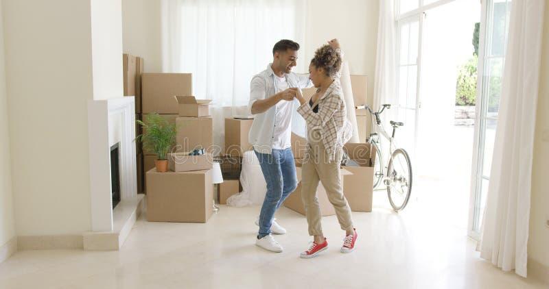 Het gelukkige jonge paar het vieren zich naar huis bewegen stock fotografie
