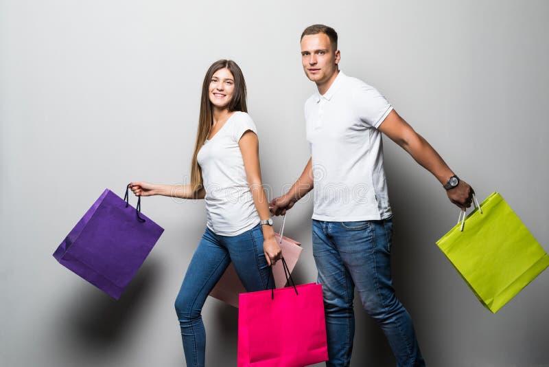 Het gelukkige jonge paar met het winkelen doet het omhelzen in zakken en het kijken weg geïsoleerd op witte achtergrond stock foto's