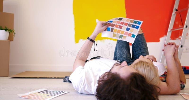 Het gelukkige jonge paar ontspannen na het schilderen stock afbeeldingen