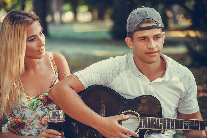 Het gelukkige jonge paar ontspannen op een picknick in aard stock fotografie