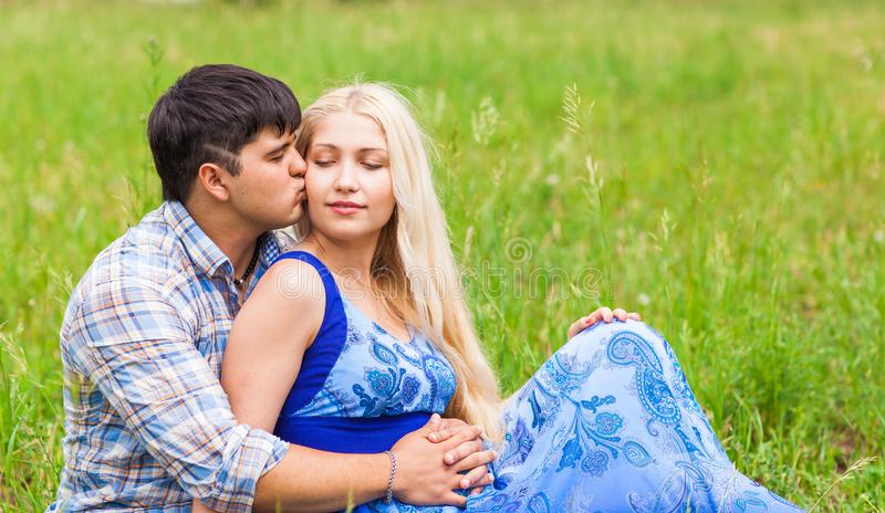 Het gelukkige jonge paar ontspannen op het gazon in een de zomerpark Het concept van de liefde Vakantie stock fotografie
