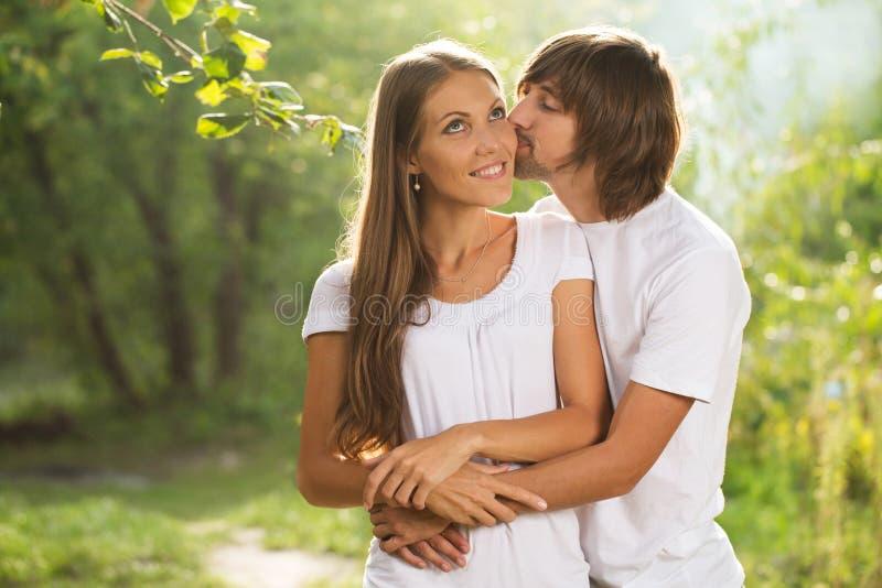 Het gelukkige jonge paar openlucht kussen stock foto
