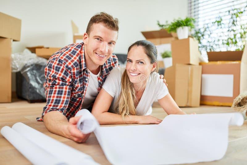 Het gelukkige jonge paar plant de huisbouw stock foto
