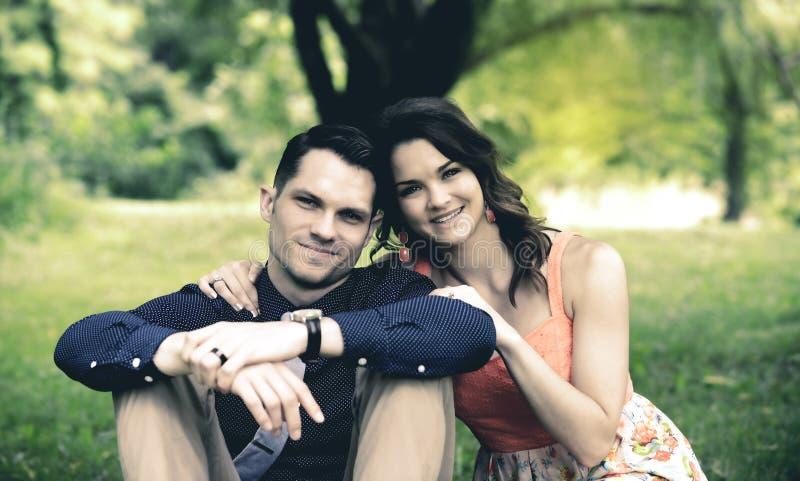 Het gelukkige jonge paar stellen ter plaatse gezet in een tuinsetti stock afbeeldingen
