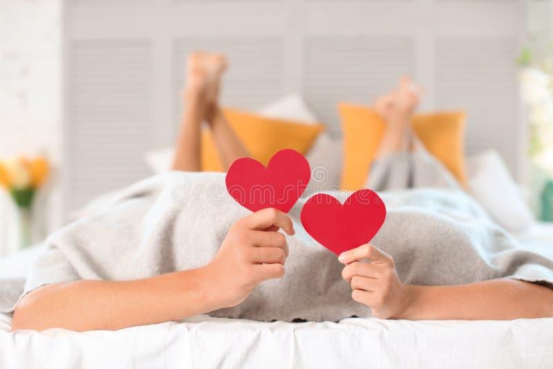 Het gelukkige jonge paar verbergen onder deken terwijl thuis het houden van rode harten op bed stock fotografie
