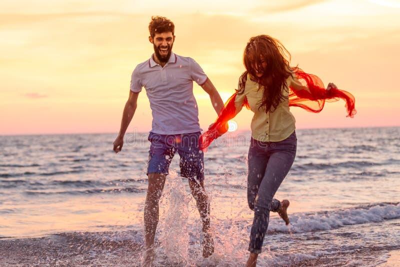 Het gelukkige jonge romantische paar in liefde heeft pret op mooi strand bij mooie de zomerdag stock afbeelding